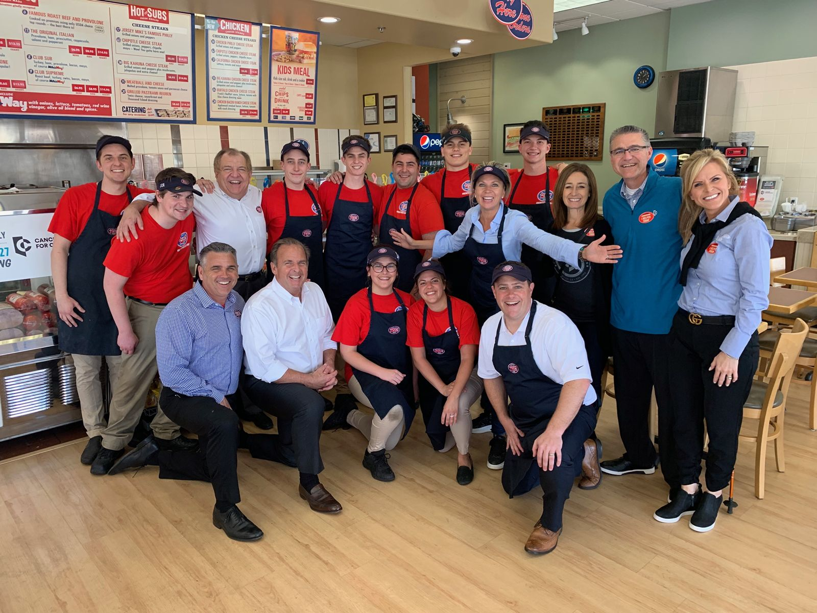 Founder & CEO Peter Cancro (kneeling, 2nd from left) celebrating Jersey Mike's 9th Annual Day of Giving in 2019.